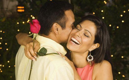 Обои Счастливая девушка обнимает парня держа в руке красную розу