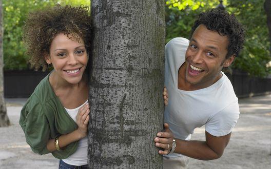 Обои Счастливая девушка и парень выглядывают из-за дерева