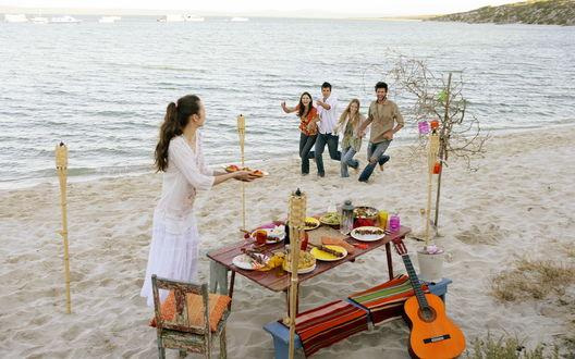 Обои Пикник на природе, друзья собрались у берега моря в теплой компании, чтобы поесть вкусной еды и попеть песни под гитару