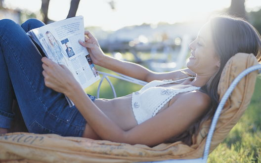 Обои Улыбающаяся девушка читает газету