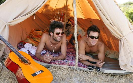 Обои Два счастливых друга лежат в палатке рядом с гитарой