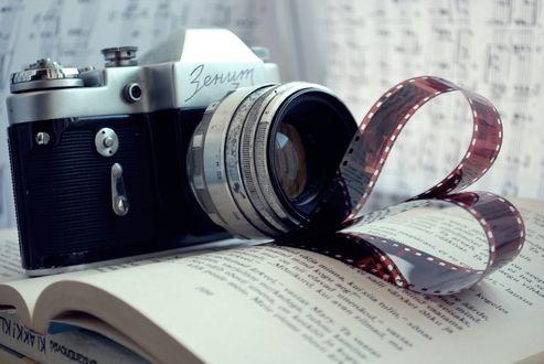 Обои Фотоаппарат «Зенит» лежит на раскрытой книге, нотах и пленке свернутой в форме сердечка
