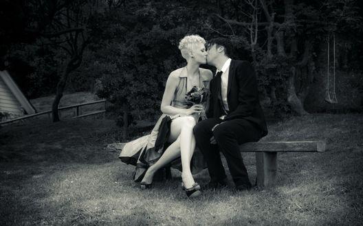 Обои Девушка и парень сидят на лавочке и целуются