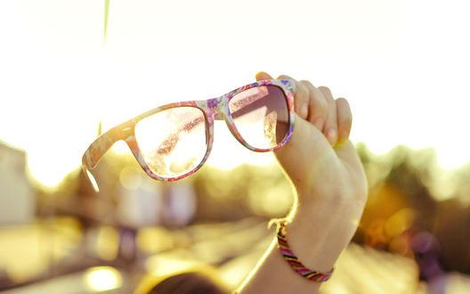 Обои Девушка протягивает руку держа в ней разноцветные очки