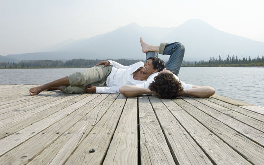 Обои Влюбленные молодые люди лежат на пристани и заливисто смеются