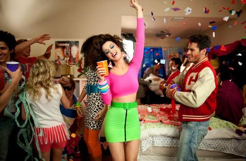 Обои Веселая молодежная вечеринка дома, брюнетка с оранжевым стаканом в салатовой юбке и розовом топе, в брекетах, подняла руку вверх