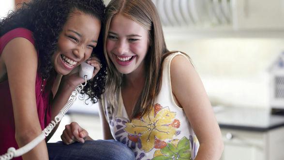 Обои Дву девушки: блондинка и брюнетка сплетничают по телефону