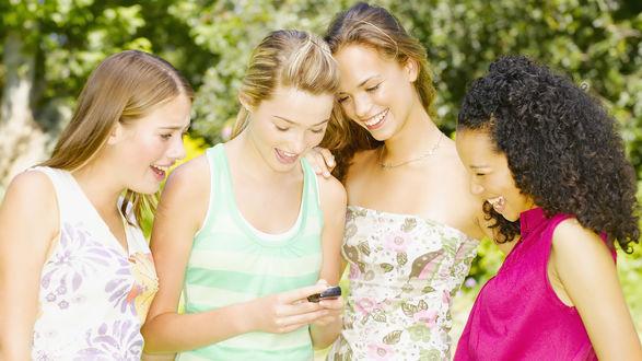 Обои Девушка делится смешной смс с подружками