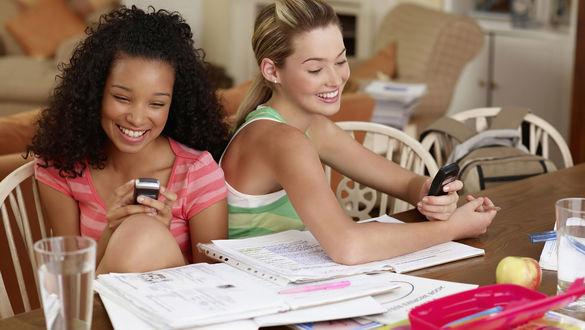 Обои Две девушки сидят за столом с бумагами и пишут СМС на мобильных телефонах