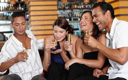 Обои Молодые люди сидят в баре с выпивкой в руках и весело смеются