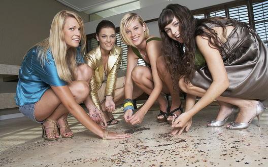 Обои Четыре красивых девушки - две блондинки и две брюнетки, в голубом, золотом, сером и зеленом нарядах с браслетами на руках  собирают разбросанное  конфетти с пола