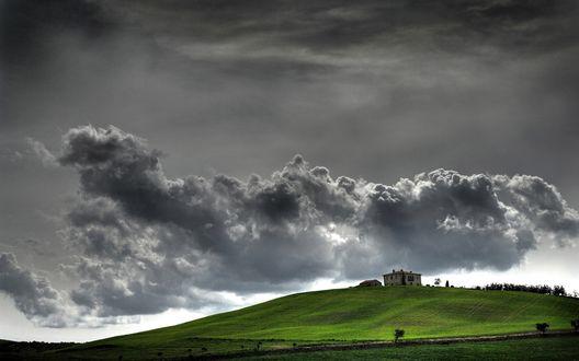 Обои Дом на зелёном холме под серым грозовым небом