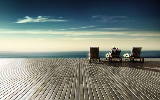 Обои Человек отдыхает в шезлонге на веранде с видом на море