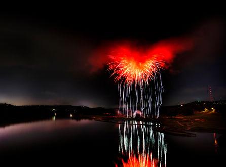 Обои В ночном небе салют в виде огненного сердца, который запускают с берега реки