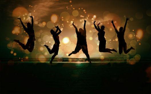 Обои Силуэты молодых людей, которые веселятся, прыгая на берегу моря на фоне заката, среди золотистых бликов