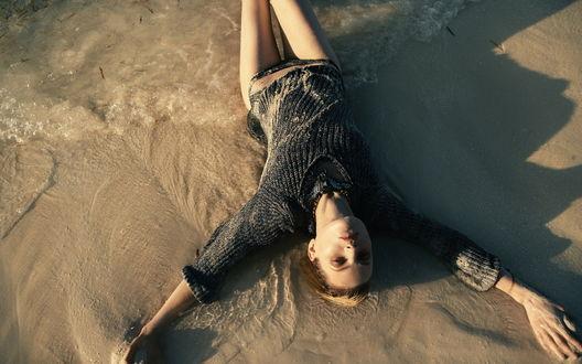 Обои Девушка в вязаном свитере лежит на песке раскинув руки, ее голые ноги омывает прохладная морская вода