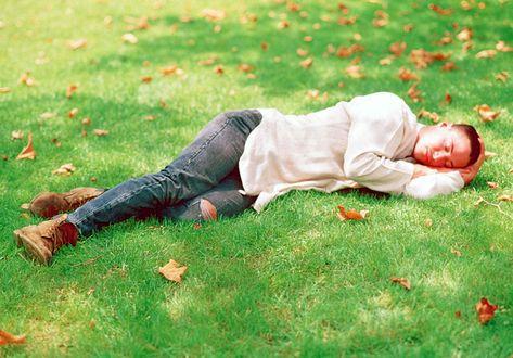 Обои Keanu Reeves / Киану Ривз дремлет на зеленой поляне, усыпанной желтыми кленовыми листьями, в белой рубашке и джинсах