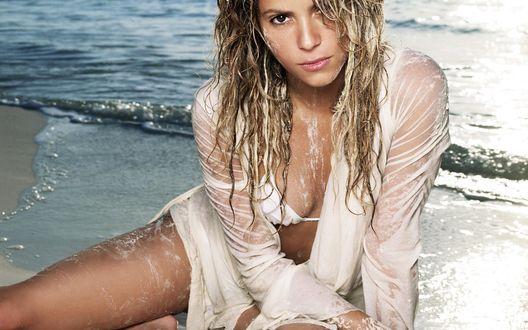 Обои Певица Шакира / Shakira сидит на пляже в мокрой рубашке, вся перепачканная в песке, прилипшем к мокрой коже
