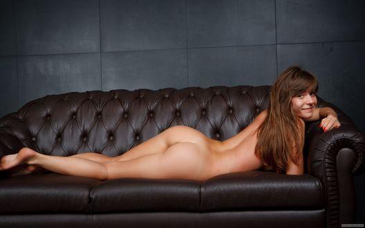 Обои Обнаженная девушка лежит на кожаном диване