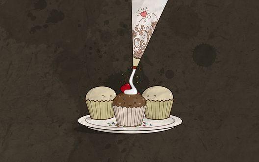 Обои Три пирожные-кексы на тарелке поливают белым кремом и посыпают глазированной присыпкой