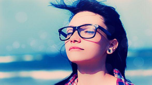 Обои Красивая девушка в очках с черной оправой и пирсингом в ухе закрыла глаза и наслаждается морским ветром