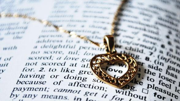 Обои Золотой кулон на цепочке в виде сердечка на странице книги
