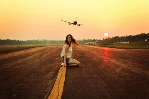 Обои Девушка в джинсовых шортах и белой майке сидит на коленях на взлетно-посадочной полосе на фоне улетающего самолета и солнца на закате