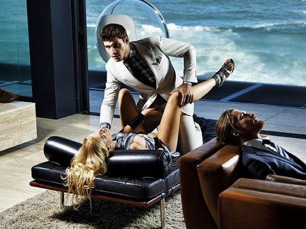Обои Парень и девушка в откровенной позе на кушетке в гостиной с видом на море, рядом на диване сидит еще один парень в рекламной кампании бренда Shameless / Бесстыдный
