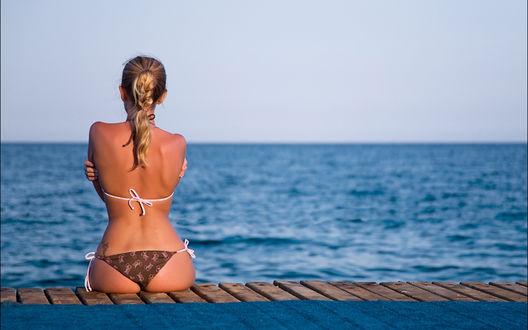 Обои Блондинка в купальнике сидит на пирсе и смотрит на синее море