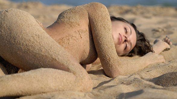 Обои Обнаженная девушка в песке лежит на пляже