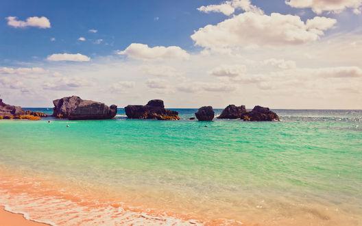Обои Море изумрудного цвета омывает пляж, чуть дальше виднеются скалы