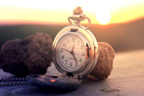 Обои Карманные серебряные часы на цепочке лежат рядом с двумя камнями на фоне восхода солнца (Quartz)