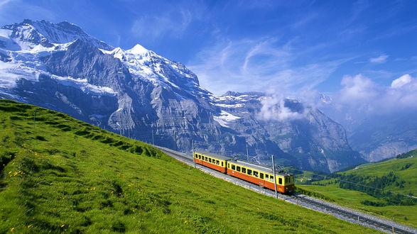 Обои Поезд едет по железной дороге, ведущей в горы