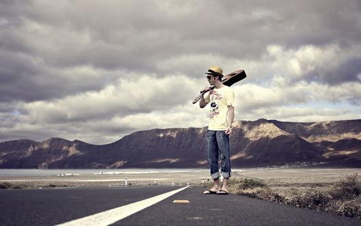 Обои Парень с гитарой стоит на дороге, ведущей к горам, над ним повисли грозовые тучи