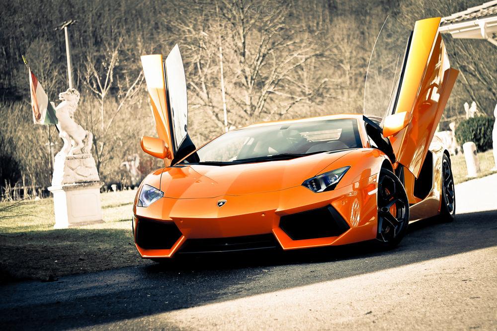 Обои для рабочего стола Оранжевая Lamborghini Aventador, LP700-4 / Ламборгини Авентадор с поднятыми дверьми среди статуй