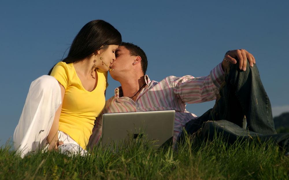 Обои для рабочего стола Парень и девушка целуются, сидя на траве с ноутбуком