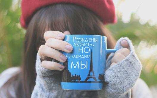 Обои Девушка в красном берете и свитере держит в руках голубую кружку с нарисованной Эйфелевой башней и надписью 'Рождены любить, но ненавидим мы'