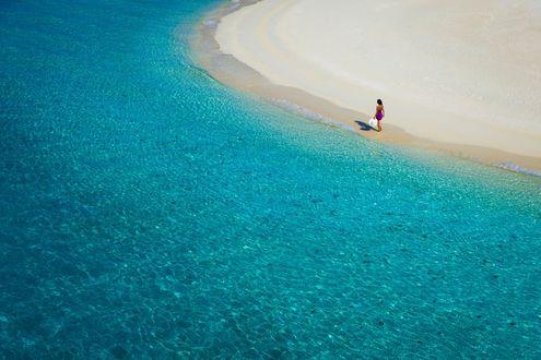Обои Девушка, с белой шляпой в руке, идет по пляжу