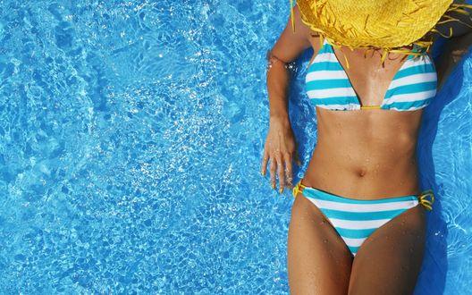 Обои Девушка в полосатом купальнике и соломенной шляпе лежит в бассейне
