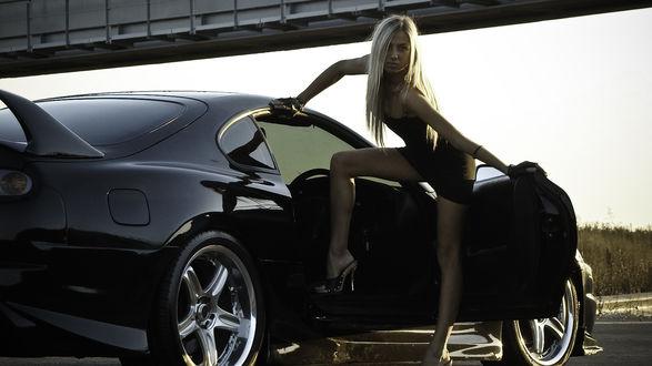 Обои Стройная и грациозная блондинка в облегающем коротком черном платье открыла дверь автомобиля
