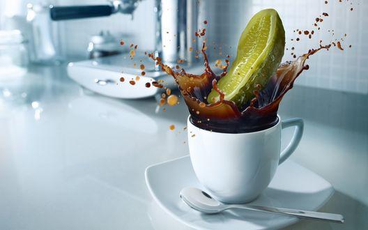 Обои Половинка солёного огурца точно спланировала в чашку с кофе, разбрызгивая её по белоснежному столу и стенам
