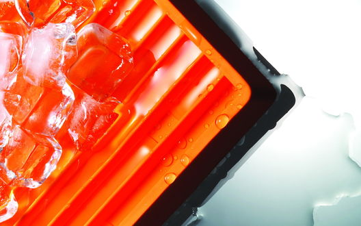 Обои Лед превращается в воду, лежа на оранжевой подложке