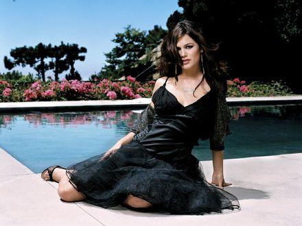 Обои Рэйчел Билсон / Rachel Bilson в черном платье сидит у бассейна, возле которого растут цветы