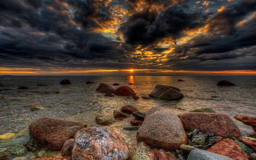 Обои Камни на морской отмели на фоне заходящего солнца, под тёмными грозовыми облаками