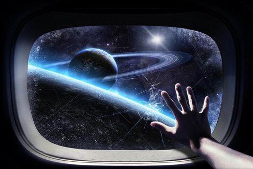 Обои Рука человека на треснувшем стекле иллюминатора за которым видны звёзды и планеты