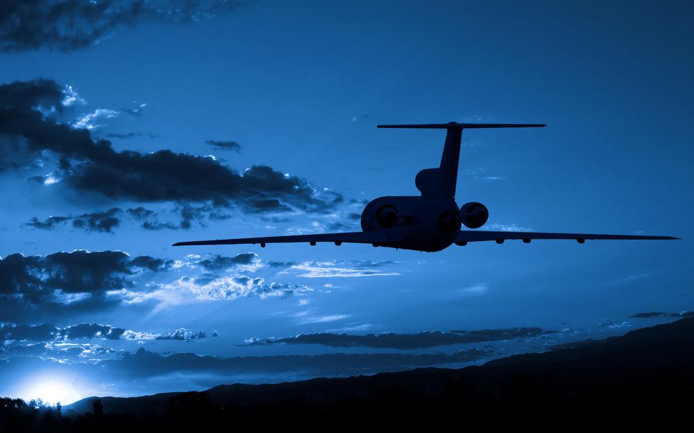 Обои для рабочего стола Самолет в синем небе летит к солнцу, скрывающемуся за горизонт