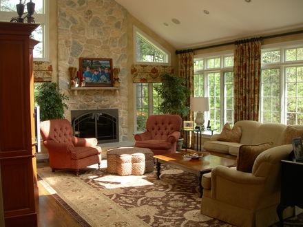 Обои Интерьер гостиной с камином, мягкой мебелью и красивым ковром, за окнами - зеленый сад