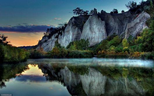 Обои Красивое горное озеро заросшее  по берегам  густым  зеленым кустарником на фоне заката