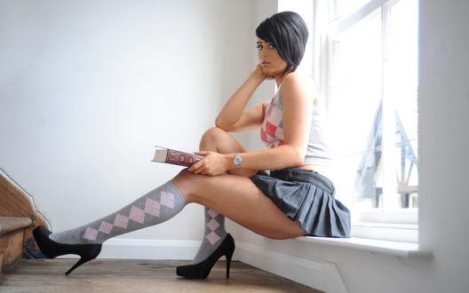 Обои Девушка с книгой в носках в ромбик и короткой серой юбке сидит на низком подоконнике