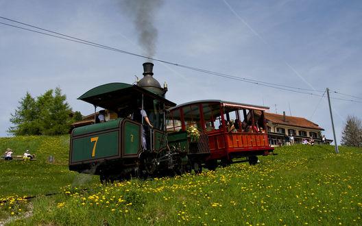Обои Небольшой старинный паровоз с прицепленным пассажирским вагоном приближается к станции с ожидающими пассажирами для совершения поездки по живописным местам
